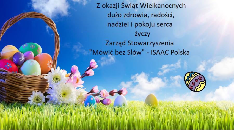 Na zielonej łące stoi koszyk z kolorowymi pisankami, obok leżą kwiaty. Na tle błękitnego nieba zamieszczone są życzenia wielkanocne.